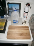 water jug<br /><br /><br /><br /><br /><br /><br /><br /> sink covered<br /><br /><br /><br /><br /><br /><br /><br /> by cutting board